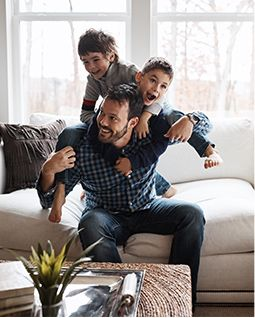 Father smiling with two young sons on his back